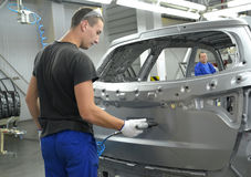 Il giovane operaio perfora un'apertura in una carrozzeria un pneumodrill Fotografia Stock