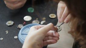 Il giovane orologiaio femminile sta mettendo le ruote dentate sulla giusta posizione in orologi video d archivio