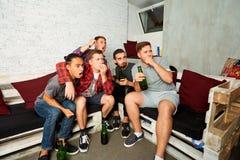 Il giovane orologio TV di ragazzo-fan, si rilassa, si diverte e beve la birra amico Immagine Stock