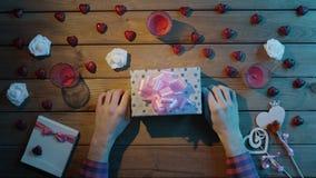 Il giovane ottiene la festa presente in contenitore di regalo sulla tavola di legno, vista superiore video d archivio
