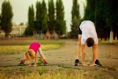 Il giovane padre atletico e la piccola figlia fanno gli esercizi in stadio fotografia stock libera da diritti
