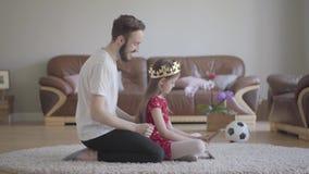 Il giovane padre bello ha vestito la testa della sua piccola figlia dai capelli lunghi sveglia con la corona ed è felice stock footage