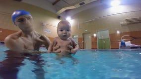 Il giovane padre con il bambino nello stagno Nuoto toracico nello stagno Un complesso degli esercizi con un infante video d archivio