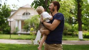 Il giovane padre con la barba in abbigliamento casual sta tenendo nelle armi il suo piccolo figlio biondo Piedi nudi del ragazzo  archivi video