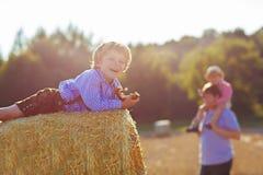 Il giovane padre e suo piccolo il figlio che si divertono sul fieno giallo sistemano la i Fotografia Stock Libera da Diritti