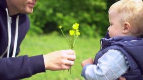 Il giovane padre felice fiuta i fiori e dà un piccolo figlio all'annusata archivi video