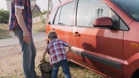 Il giovane padre mostra al suo piccolo bambino sveglio come lavare la loro automobile rossa con il movimento lento dell'acqua del video d archivio