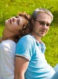Il giovane paio si siede su un'erba Fotografia Stock Libera da Diritti