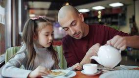 Il giovane papà con una piccola figlia mangia la pizza ed il tè in pizzeria Cibo degli alimenti a rapida preparazione video d archivio