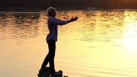 Il giovane pratica l'yoga sulle radici dell'albero al tramonto archivi video