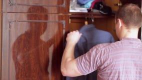 Il giovane prende una camicia dal gabinetto stock footage