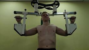 Il giovane prepara i muscoli pettorali nella palestra, facente la forma fisica