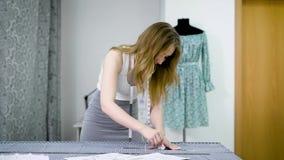 Il giovane progettista femminile con il nastro-line sul suo collo che sta nello studio di sartoria e che disegna allinea con gess archivi video