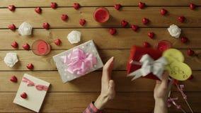 Il giovane prova a capire che cosa si trova dentro i suoi regali di festa e li scuote, vista superiore archivi video