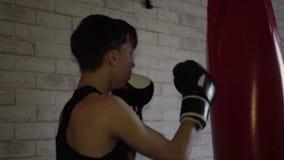 Il giovane pugile professionista pratica la tecnica di colpi nell'addestramento, archivi video