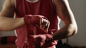 Il giovane pugile tira la fasciatura rossa sulle mani e sulle pose di lotta archivi video