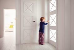 Il giovane ragazzo apre la porta a casa fotografia stock