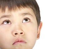 Il giovane ragazzo asiatico sveglio osserva in su con un fronte triste Immagine Stock