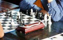 Il giovane ragazzo astuto sveglio in camicia blu gioca gli scacchi sull'addestramento prima del torneo campeggio estivo di scacch fotografia stock