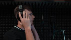 Il giovane ragazzo attraente sta cantando emozionalmente L'uomo bello sta sorridendo allo studio di registrazione professionale archivi video