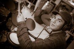 Il giovane ragazzo caucasico biondo gioca i tamburi in negozio immagine stock