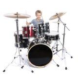 Il giovane ragazzo caucasico gioca i tamburi in studio contro il backgrou bianco Fotografia Stock Libera da Diritti