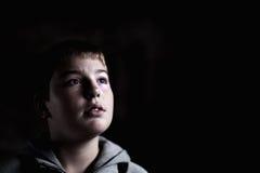 Il giovane ragazzo che osserva in su con la speranza in suo eyes scuro Fotografia Stock