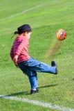 Il giovane ragazzo dà dei calci alla sfera di gomma. Fotografie Stock