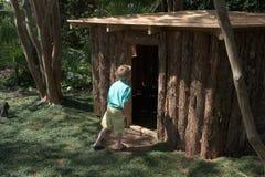 Il giovane ragazzo entra in una casa del gioco ad un giardino all'aperto Fotografie Stock