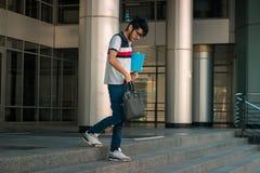 Il giovane ragazzo esile sta stando sulla via con un libro Fotografie Stock