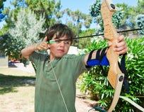 Il giovane ragazzo fa il tiro all'arco immagine stock libera da diritti