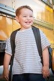 Il giovane ragazzo felice attende per imbarcarsi sul bus per il banco Fotografia Stock