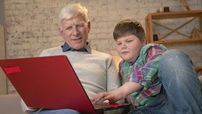 Il giovane ragazzo grasso insegna a nonno a come utilizzare un computer portatile Differenza delle generazioni Comodità domestica stock footage