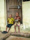 Il giovane ragazzo indiano due si è seduto sulla porta a sua casa fotografia stock