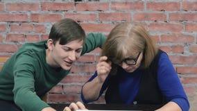 Il giovane ragazzo insegna ad uso anziano della nonna ad un computer portatile helping Priorità bassa del muro di mattoni stock footage