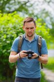 Il giovane ragazzo intraprende la macchina fotografica nel parco fotografia stock