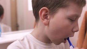 Il giovane ragazzo schiaccia il dentifricio in pasta sullo spazzolino da denti e pulisce i denti archivi video