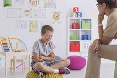 Il giovane ragazzo si siede su un pouf giallo Fotografia Stock