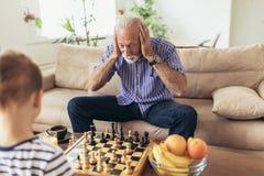 Il giovane ragazzo sta giocando gli scacchi con suo nonno fotografia stock