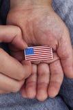 Il giovane ragazzo tiene il distintivo della bandiera americana in sue mani Fotografie Stock Libere da Diritti