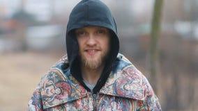 Il giovane in retro cappotto d'annata con il cappuccio nero e la barba marrone che guarda nella macchina fotografica in campagna  stock footage
