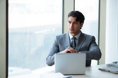 Il giovane riuscito uomo d'affari che lavora all'ufficio immagine stock