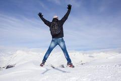 Il giovane salta per la gioia nelle montagne nevose Fotografia Stock