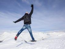 Il giovane salta per la gioia nelle montagne nevose Immagini Stock Libere da Diritti