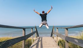 Il giovane salta sulla spiaggia sopra un percorso di legno al Mar Baltico sopra fotografie stock libere da diritti