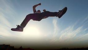 Il giovane saltatore maschio del tricker di Parkour esegue le vibrazioni di stupore, siluetta stock footage