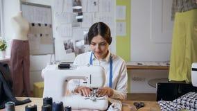Il giovane sarto femminile che lavora alla macchina per cucire in cuce lo studio video d archivio