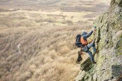 Il giovane scala la roccia su una corda con le cinture di sicurezza, assicurazione e corda, nell'attrezzatura piena di alpinismo  Immagine Stock