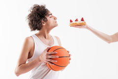 Il giovane scarno è sedotto da alimento non sano dolce Immagini Stock Libere da Diritti