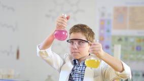 Il giovane scienziato confronta due liquidi variopinti in laboratorio video d archivio